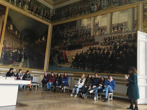 The tour of the Château de Versailles began in a vast room decorated with impressive paintings.
